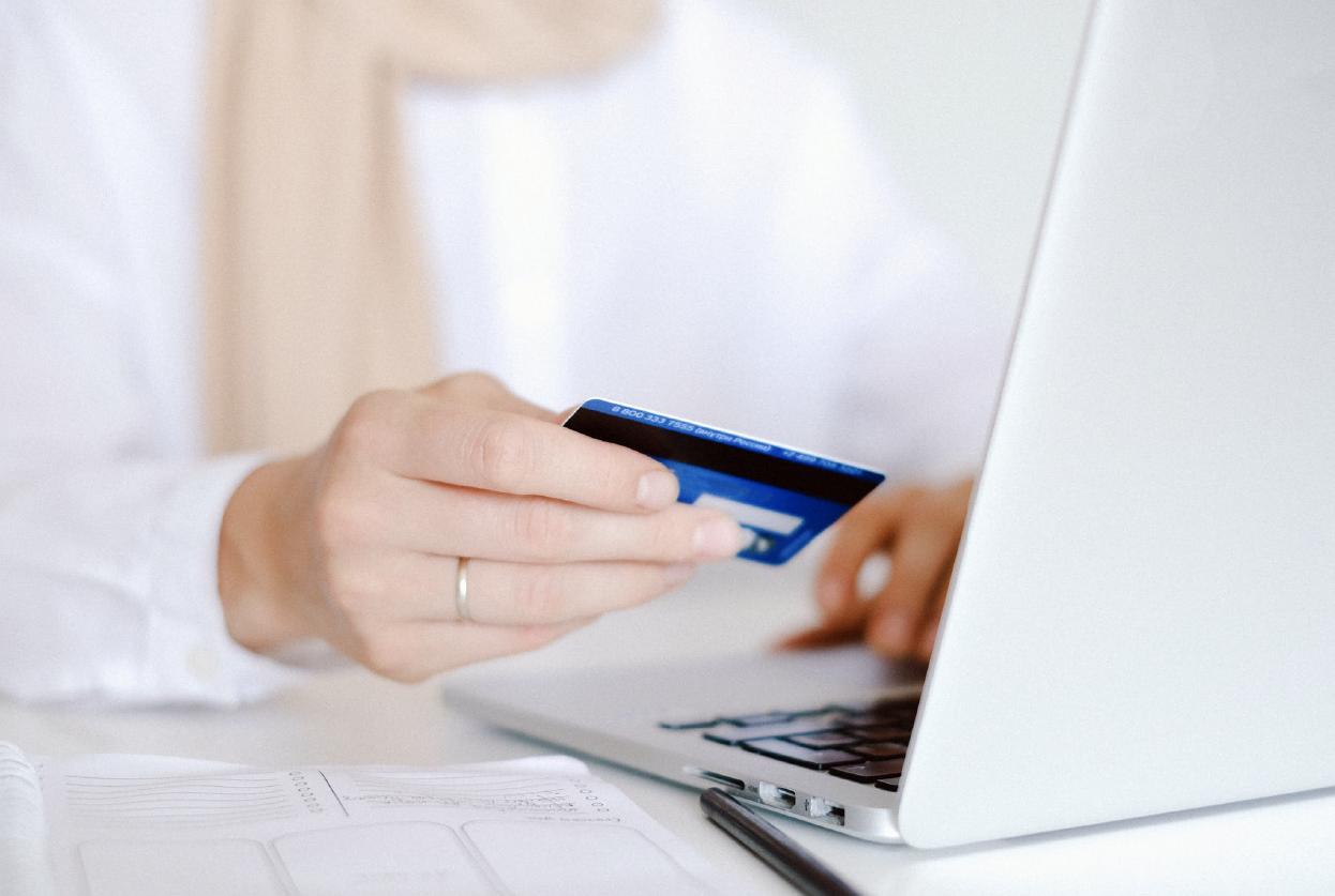 Persona sosteniendo tarjeta frente a una computadora