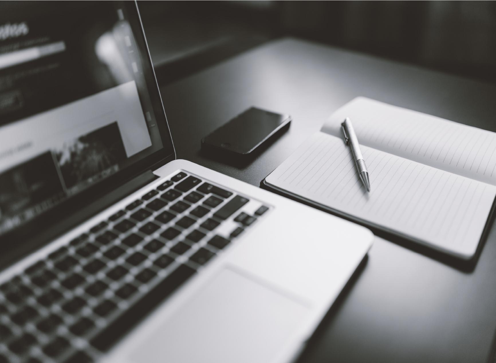 Escritorio con una computadora y un anotador al costado